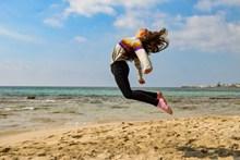 海边女生跳跃拍摄图片