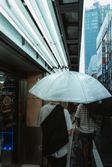 男人雨天撑伞背影高清图片