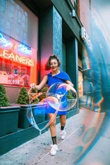 街头玩泡泡的美女图片素材
