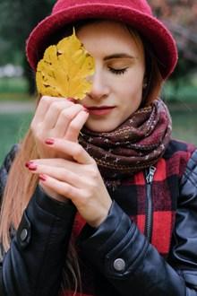 拿着树叶遮住眼睛的美女高清图片